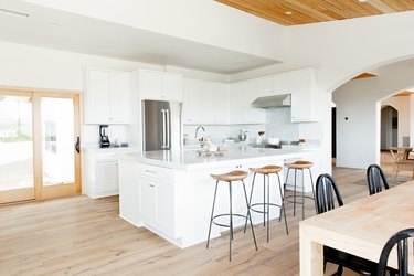 Open kitchen area with a white kitchen island. Three bar stools with wooden seats and metal legs in front of the island. Behind the island, there's a stainless steel refrigerator and white cabinets run along the wall. Next to the kitchen, sliding glass doors. In the foreground, a wooden dining table surrounded by black winsdor chairs.