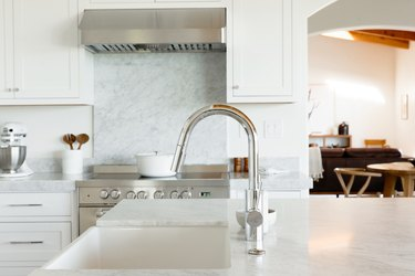 Kitchen sink in a marble countertop with a chrome faucet. Behind it, a stainless steel range with a white dutch oven on the stovetop.