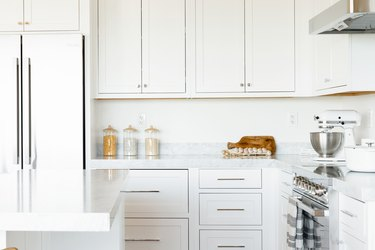Kitchen counter. The countertop itself is marble, and the cabinets above and below are white. On the counter, three glass food storage containers, a cutting board, a string of garlic, and a white KitchenAid stand mixer with a stainless steel bowl.