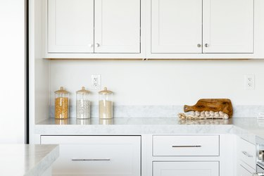 Kitchen counter. The countertop itself is marble, and the cabinets above and below are white. On the counter, three glass food storage containers, a cutting board, and a string of garlic.
