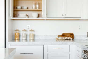 Kitchen counter. The countertop itself is marble, and the cabinets above and below are white. The top left cabinet is open, revealing a stacks of white plates,  white bowls, two white mugs, and two clear glasses. On the counter, three glass food storage containers, a cutting board, and a string of garlic.