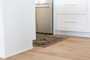 Wood floor, rug, and bottom of white cabinet drawers in a kitchen. Stainless steel oven is visible