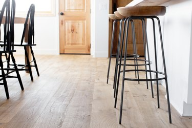 Chairs between kitchen and dining area with a pathway between leading to a wooden door. The floor is wood and the walls are white. On the right, three bar stools with wooden seats and metal legs. On the left, black Windsor chairs.