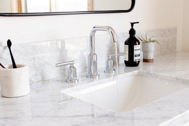 Silver faucet sink with granite or marble countertop. White container with toothbrushes, black bottle, and succulent. Mirror is above.