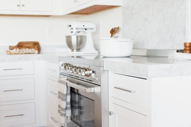 Kitchen counter with white drawers and a white marble countertop. In the middle of the counter, a stainless steel range. A white and grey striped kitchen towel is hanging over the handle over the oven door. A white dutch oven in on the stovetop, and there's a white KitchenAid stand mixer.
