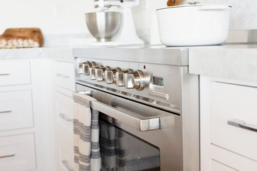 An oven door and temperature control knobs on a stainless steel range. A white and grey striped kitchen towel is hanging over the handle over the oven door.