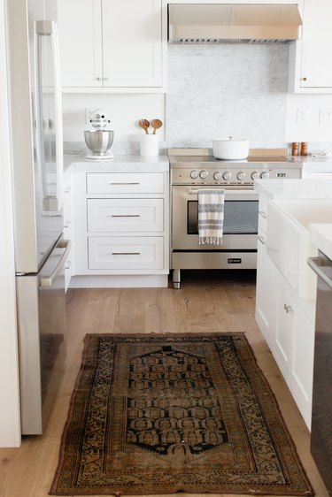 Kitchen with a stainless steel range, white cabinets, and a marble countertop. On the countertop, there's a white KitchenAid stand mixer with a stainless steel mixing bowl along with a white utensil holder with wooden salad tongs. On the stovetop, there's a white dutch oven. On the wood floor, there's a small rug.