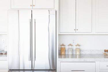 Double doors of a stainless steel refrigerator with white cabinets overhead. Next to it, marble countertop with glass food storage containers and white cabinets.