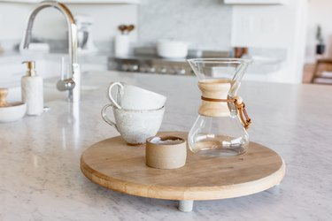 On a marble countertop, two stacked ceramic mugs, a Chemex, and a candle in a ceramic holder on a small round wooden board. In the background, a chrome faucet and a marbled soap dispenser.