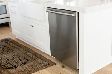 Stainless steel dishwasher in a white kitchen island. The marble countertop extends over the dishwasher. On the floor, a small rug.