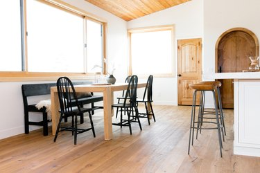 An open interior space a large dining table on one side and a white kitchen island on the other side. At the table, there are four black Windsor chairs and a black wood bench, which is against the wall. Three wooden bar stools with metal legs sit in front of the kitchen island. There are two windows lining the white walls, and two wooden doors.