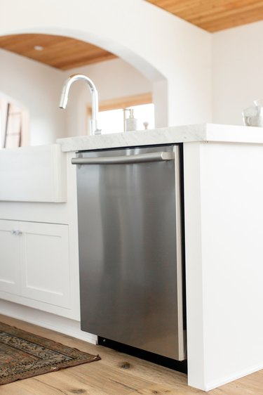 Stainless steel dishwasher in a white kitchen island. The marble countertop extends over the dishwasher. A chrome faucet is visible.