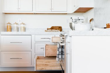 In a kitchen, white drawers with a marble countertop and white cabinets above. Three of the drawers are open to varying degrees. On the countertop, there's a white KitchenAid stand mixer, three glass storage containers, and a white pot.