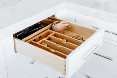 An open drawer with a wooden cutlery organizer. Cutlery, measuring cups and spoons, and other utensils visible inside. Marble countertop above the drawer.
