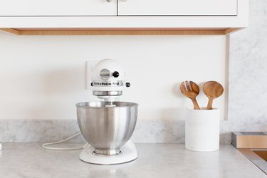 A white KitchenAid stand mixer with a stainless steel mixing bowl on a marble countertop. Next to the mixer is a white utensil holder with wooden salad tongs.