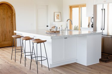 Three bar stools with wooden seats and black metal legs next to a white kitchen island with a marble countertop and chrome faucet. Behind the island is a chrome fridge.