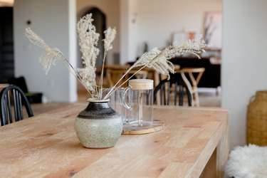 Light wood tabletop with a grey and black ceramic vase with stalks of wispy grass in it. Behind the vase, there's a glass pitcher and glasses.