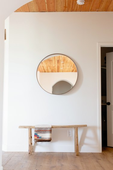 Hallway Furniture Ideas with A circular mirror on a white wall. Underneath, there's a low wooden bench with a throw blanket hanging on it.