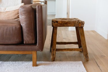 A small wooden stool next to a brown leather couch.