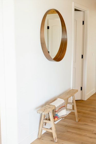A circular mirror on a white wall. Below it, a low wooden bench with a decorative throw.