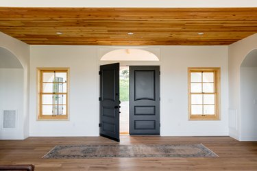 An entry hall of a Spanish-style home with double dark wood doors, one of which is open, on a white wall. Two windows with light wood frames on either side of the door. The floor and ceiling are both made of wood. There's a rug in front of the door.