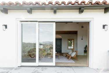 Glass sliding doors with white frame leading to a living room where two teak chairs with accent pillows and a rustic coffee table are visible.
