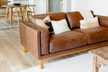 A brown leather sofa with three pillows and a white throw blanket. The sofa is on a white rug, and a wood coffee table is visible. Behind the sofa, there is a light wood table with four chairs and a dark brown bowl in the center of the table.