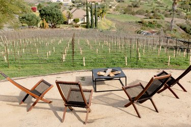 Dirt patio area with four wooden and rope lounge chairs and a fire pit. The seating area overlooks a young vineyard.
