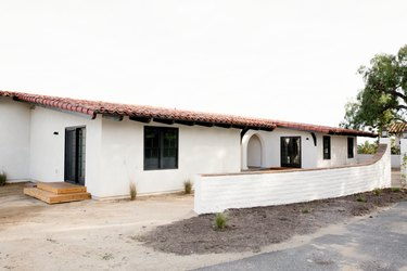 Main and side entrances of a white Spanish-style home with a clay tiled roof. A white brick perimeter wall runs in front of the home. An archway leading to the front door is visible. Two wooden steps lead up to the side entrance.