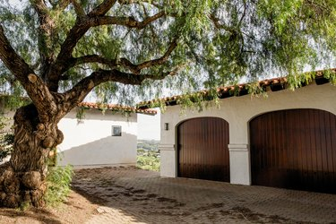 Brick driveway leading to a white Spanish-style garage with two sleek wooden doors. A large oak tree grows on the other side of the driveway, its branches reaching towards the garage.