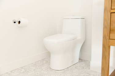 A white toilet in a bathroom with white walls and a white and grey tiled floor. A roll of toilet paper is on the wall next to the toilet, hanging on a simple chrome holder.
