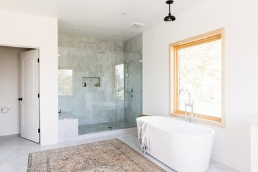 Bathroom with a freestanding bathtub, marble/granite shower with glass doors,  bell pendant light, neutral rug, and wood frame window.