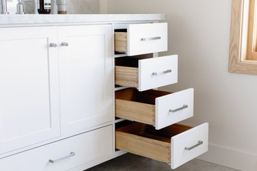 white bathroom vanity with four open drawers