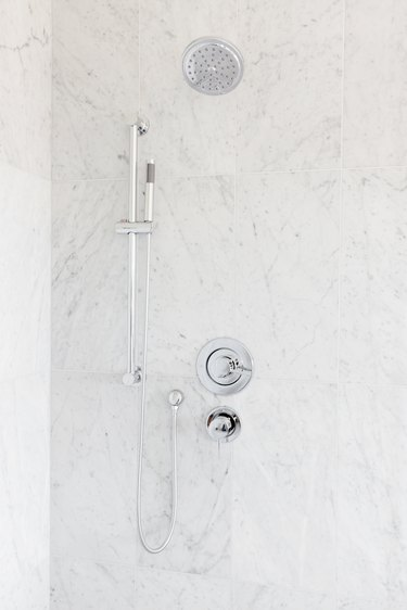 Silver rain shower head, hand held shower head, and faucet handle. Gray marble or granite shower walls.