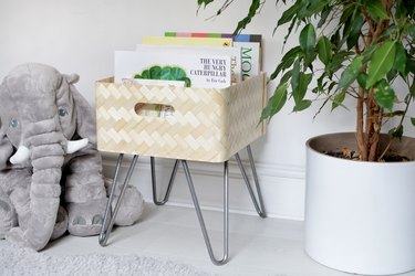 Light tan book bin with metal legs and picture books in a white room next to elephant stuffed animal and medium-sized plant