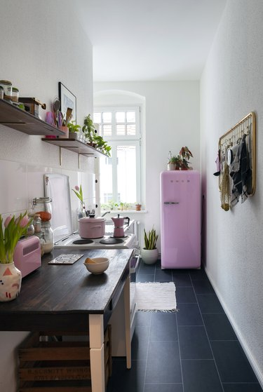 small narrow kitchen with black tile floors and pink smeg fridge