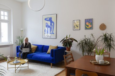 blue velvet sofa in eclectic boho living room with lots of houseplants and modern art