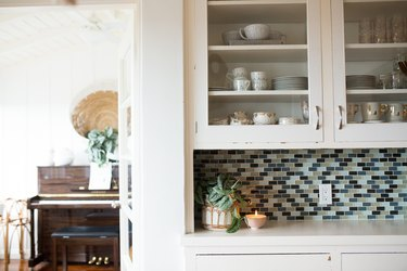 A white kitchen cabinet with dish ware, and a blue-neutral backsplash.