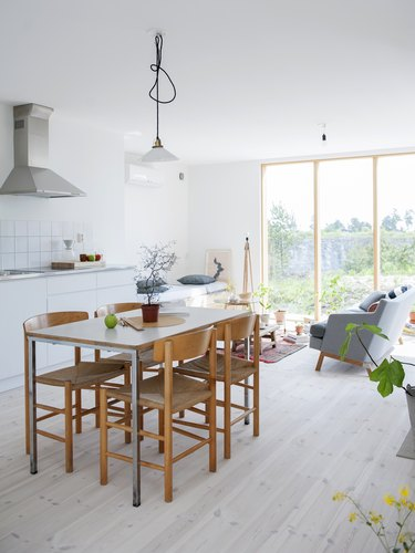 a simple wooden dining table and wooden chairs on a light wood floor in a bright white kitchen