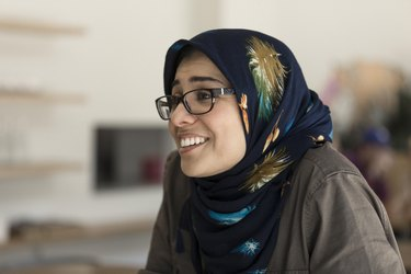 maryam eskandari smiling, wearing  glasses and a headscarf