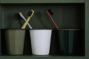 Green and white cups with toothbrushes in forest green cabinet