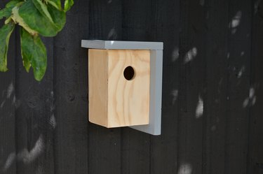 Minimalist wood birdhouse with painted gray roof against black fence