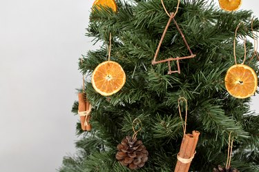 Tree with ornaments made from dried orange slices, pinecones, twigs and cinnamon sticks