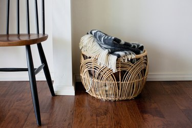 Rattan, curved arch basket with a blanket, and a wood chair on a hardwood floor