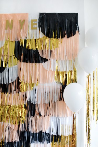 DIY NYE backdrop with scalloped paper fringes in black, white, pink, and gold, with white balloons in a white room