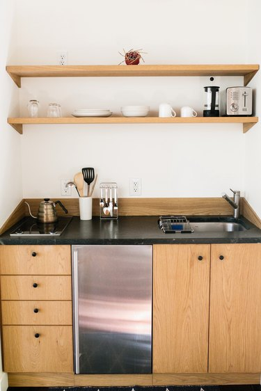 kitchenette with light wood cabinets, black counters, two shelves, a mini fridge, and small stovetop