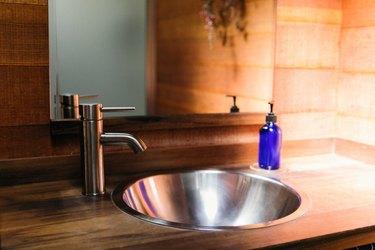 Midcentury Modern Bathroom Sink and paneled walls, round metal sink, faucet, mirror.