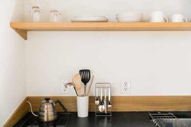 A wood shelf with white chinaware. A black counter with a metal teapot and dish ware organizers.