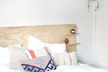 a headboard made out of a sheet of unfinished plywood with two shelves mounted on it