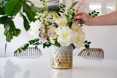 Hand placing white and pink flowers in a vase with green leaves